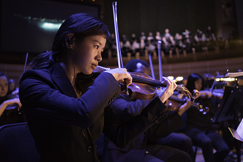 Frost School's Henry Mancini Orchestra student playing the violin during a performance
