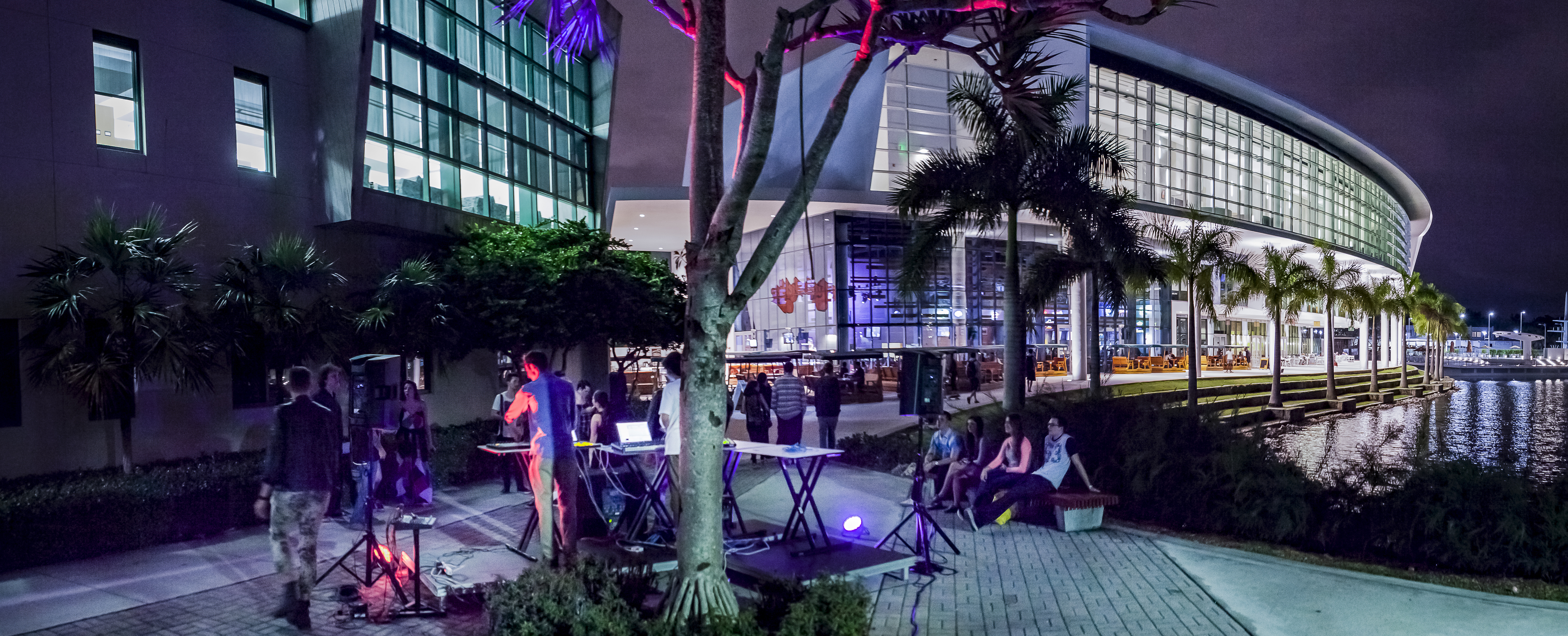 A pair of musicians playing electronic music in a impromptu setup while some spectators observe, at the University of Miami campus.