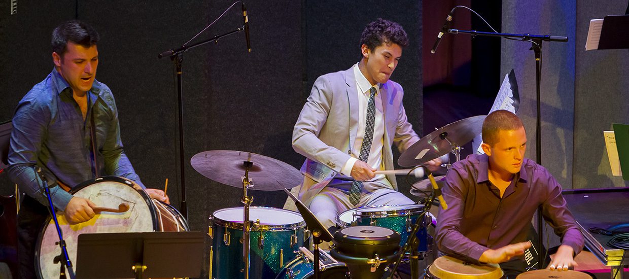 A group of musicians in suits play different percussion instruments live on stage.