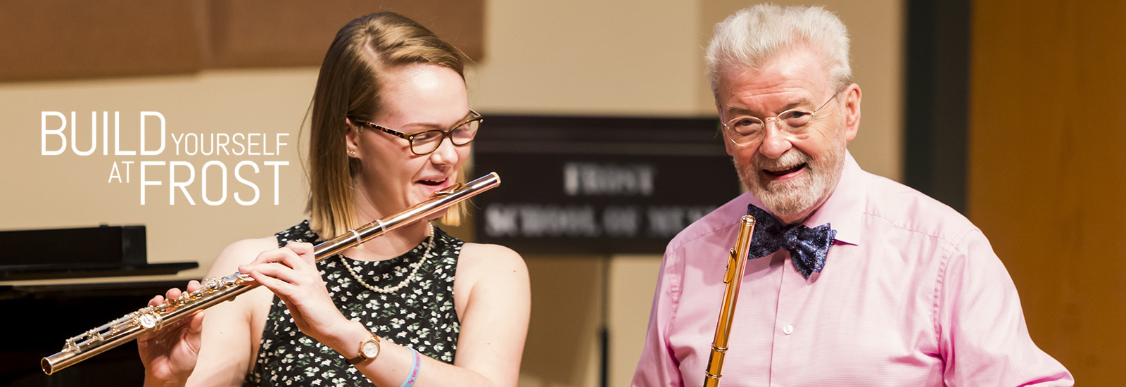 A blonde woman with glasses is smiling as she plays the flute while an older man with glasses holding a flute smiles at the camera.
