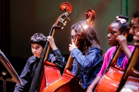 A diverse group of children play cellos on stage during a performance.