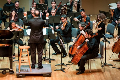 A conductor in a suit standing on a platform conducts an orchestra while they sit around him.