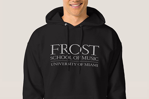 A man wearing a black sweatshirt showcasing the words FROST School of Music
