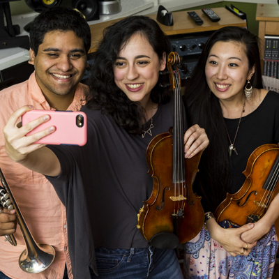 Three students take a selfie in a recording studio as they all hold up their instruments